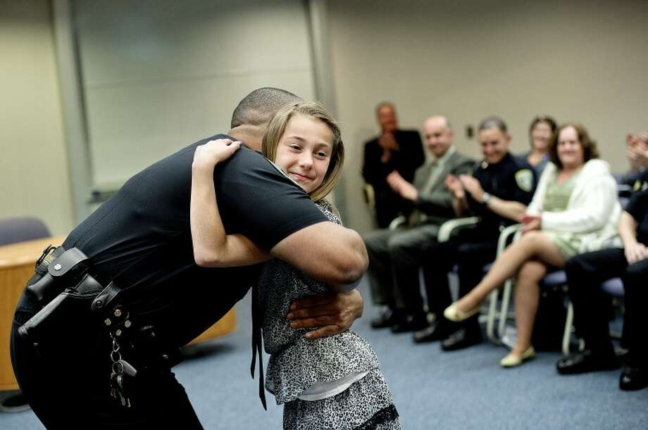 NICK KING | nking@mdn.netMidland Police Officer Corey Armstead hugs family friend Janelle Lewis, 10, after she pinned Armstead's badge over his heart Tuesday during a swearing-in ceremony in the Council Chambers at Midland City Hall. Lewis said that it was scary pinning the badge because she didn't want to poke Armstead with the pin. Armstead, Michael Bess and Joshua Thielen were all sworn in as police officers during the ceremony. Photo: Nick King