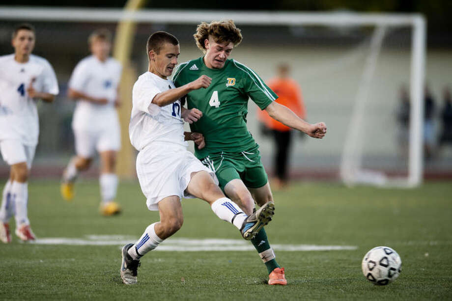 NEIL BLAKE | nblake@mdn.netMidland's Luke Ewbank kicks the ball in front of Ethan Loftis during the game at Midland Community Stadium on Wednesday. Photo: Neil Blake/Midland  Daily News