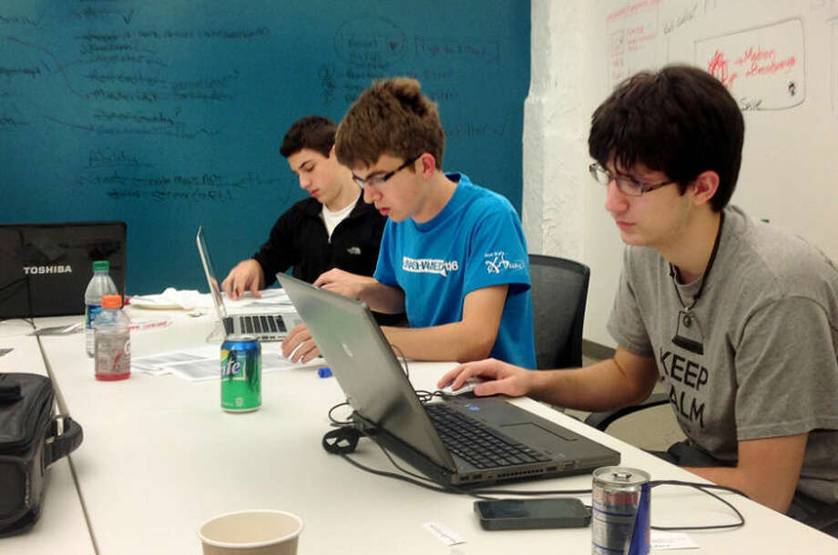 ROGER BRYANT | for the Daily News From left, Midland High School seniors Richard Doktycz, Aaron Green and Thor Russell work on developing an app at the Code Michigan contest, held Oct. 4-6 in Detroit.