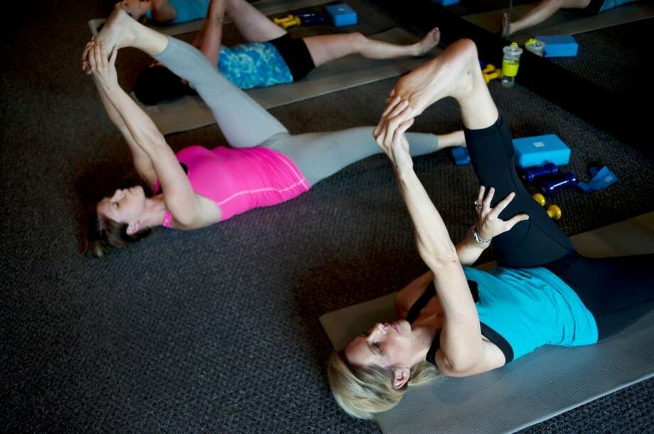 NEIL BLAKE | nblake@mdn.net Element 22 co-owners Jennifer Gracey, right, and Jennifer Glackin, left, stretch out during a Barre Intensity class on Wednesday at the fitness studio. The hour long class, led by Gracey, is designed to strengthen and lengthen muscles. Gracey recommends doing the workout three times a week. Photo: Neil Blake/Midland  Daily News