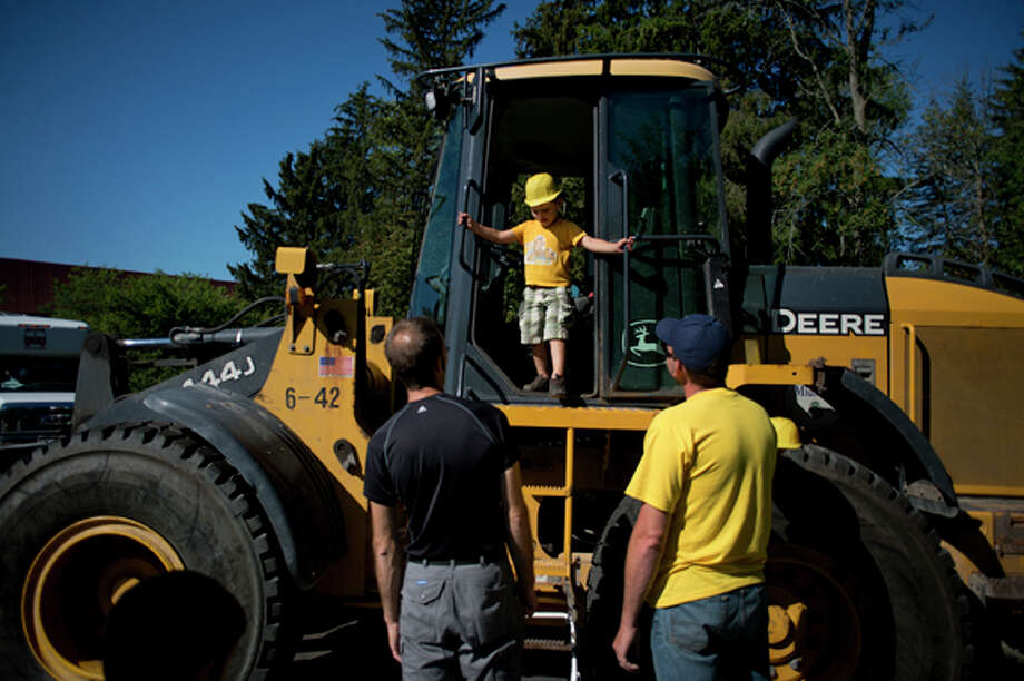 "Henry Kosick, 3, looks down from a front end loader at his father, Andy, as equipment operator Ryan Anderson stands by at the Grace A. Dow Memorial Library for ""Touch a Truck"" on Thursday. Photo: Neil Blake/Midland  Daily News / Midland Daily News"