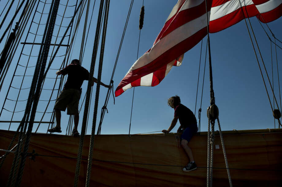 NEIL BLAKE | nblake@mdn.netDeckhand Brandon Fiew, right, works on the Pride of Baltimore II after docking in Bay City on Thursday. The Pride is a reproduction of an 1812-era Baltimore Clipper named Chausseur, saw action in the War of 1812 against the British merchant fleet.