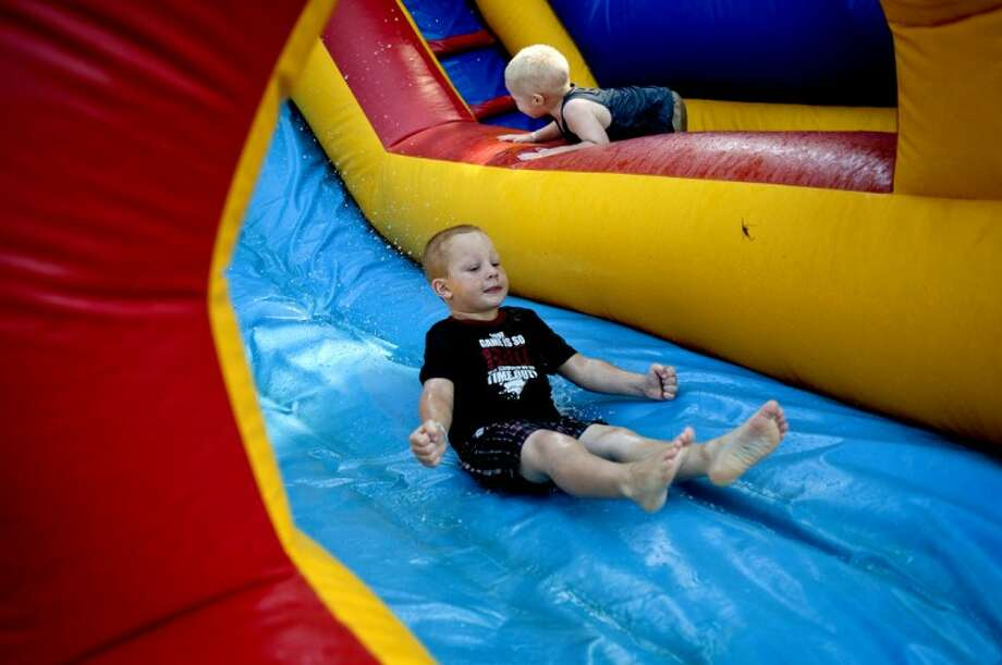 NICK KING | nking@mdn.net Nicholas Wolley, 4,left, and his brother Alexander, 2, play on an inflatable water slide Friday during the Labadie Pig Gig at Veterans Memorial Park in Bay City. The annual rib festival features music acts, family entertainment and activities and various barbecue vendors from Michigan, Ohio, South Carolina and Australia. The festival continues on Saturday and Sunday. Photo: Nick King/Midland  Daily News