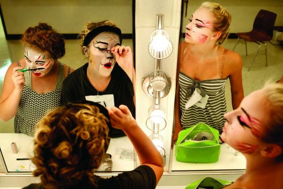 "From left, Emma Moore, 17, of Midland; Kaila Smith, 17, of Sanford and MacKenna Hartman, 15, of Midland put on false eyelashes after having their faces air brushed to look like characters in the musical ""Cats."" The 31-member cast has been practicing since the beginning of June. This is Teenage Musical Inc.'s 50th season performance. Photo: Brittney Lohmiller"