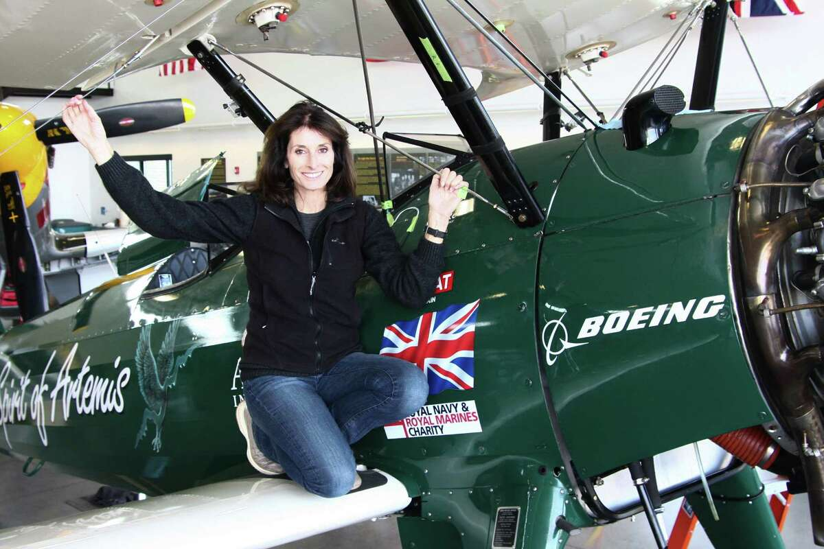 Tracey Curtis-Taylor poses for a portrait on her plane, the Spirit of Artemis, a Boeing Stearman, as it is reassembled at the Historic Flight Foundation in Mukilteo, Friday, Mar. 18, 2016.
