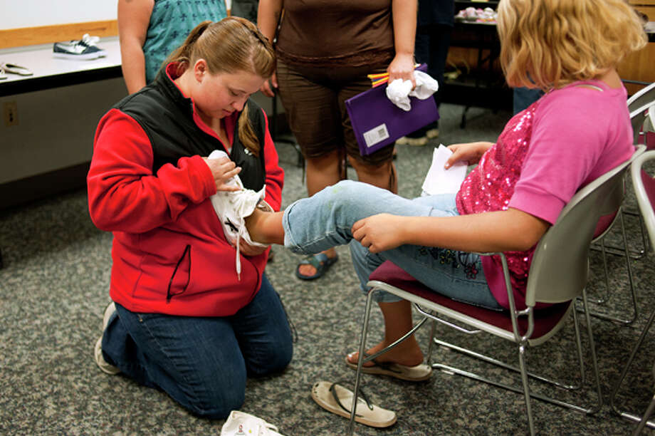 NEIL BLAKE | nblake@mdn.netVolunteer Stephanie Jackson of Hemlock helps Janelynn Knapp, 11, of Freeland, try on shoes at a back-to-school distribution at the Midland/Isabella Department of Human Services building on Friday. The Dow Chemical Michigan Operations Community Team and the Midland Noon Exchange Club teamed up for the distribution, but the demand far exceeded the supply and many families left without backpacks or shoes for the upcoming school year.