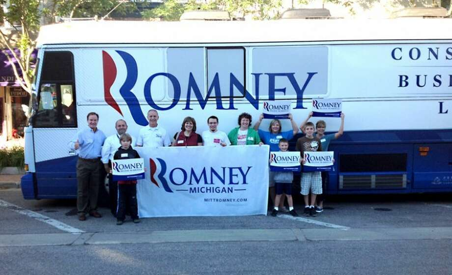 Photo providedMichigan Attorney General Bill Schuette (left) and others pose outside the Romney Mobile Headquarters bus at Journey's in downtown Midland this morning.