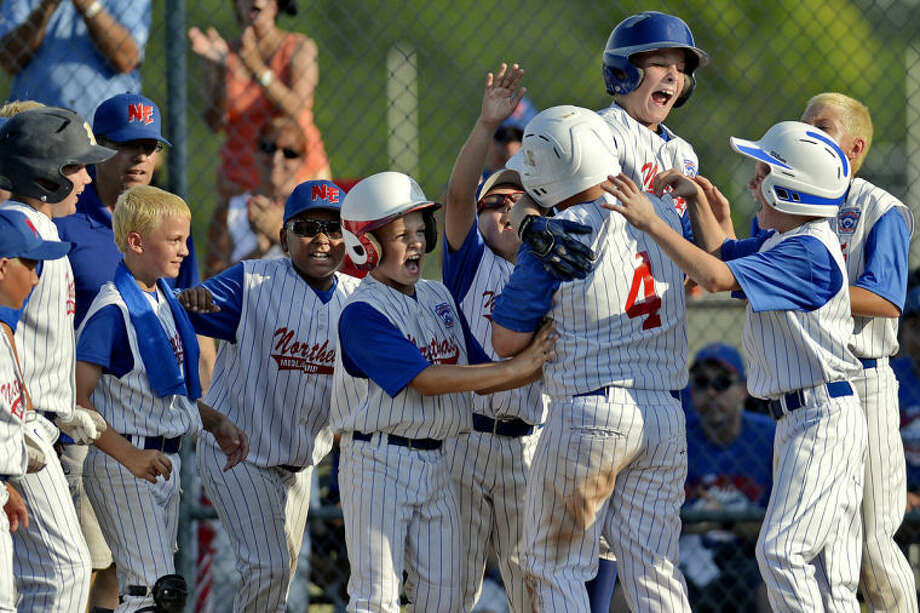 NICK KING | nking@mdn.netNortheast's Ethan Volmering (4) is greeted by teammates after his home during the fifth inning Monday at Wilson Field. Northeast won 8-1. Photo: Nick King/Midland  Daily News