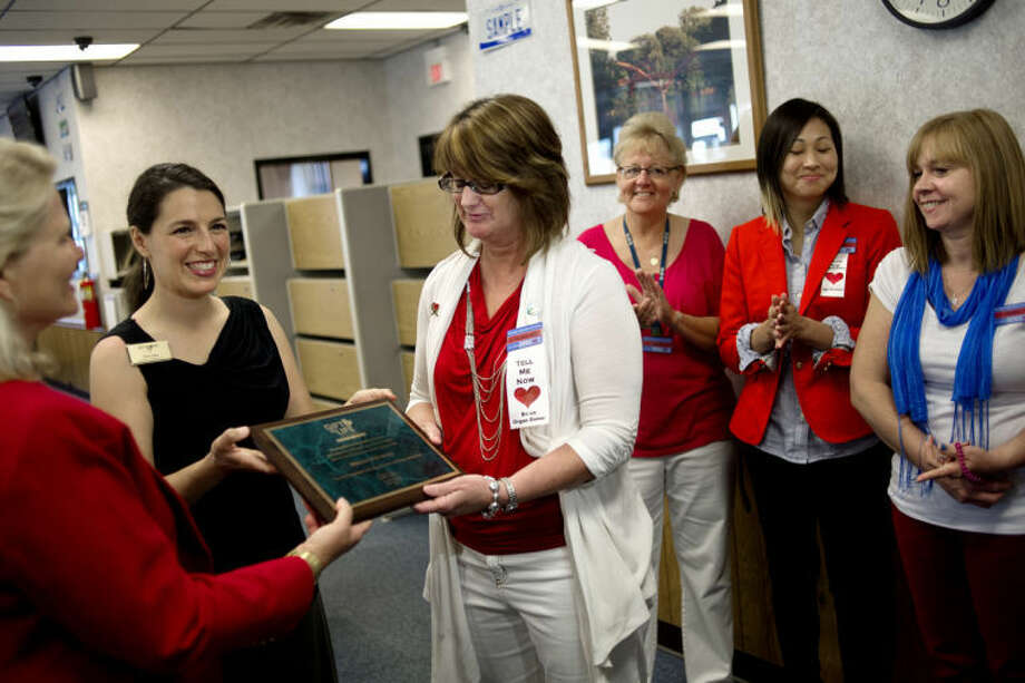 NICK KING | nking@mdn.net Secretary of State Ruth Johnson, left, and Gift of Life volunteer coordinator and SOS branch liaison Kim Zasa, center, present a plaque to employee Jackie Pappas, right, Friday at the Secretary of State office in Midland. Secretary Johnson, and Zasa presented a Gift of Life plaque to the Midland office in recognition of employees' outstanding efforts in registering organ donors. Photo: Nick King/Midland  Daily News