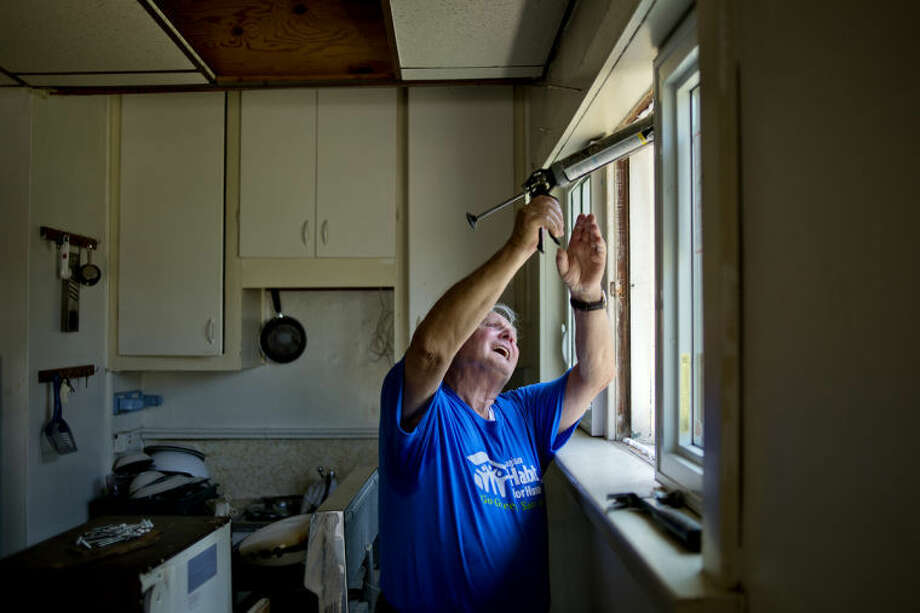 NICK KING | nking@mdn.netWalter Stuermer, of Midland, works on installing new windows in the kitchen at Gary Brahmer's home in Freeland on Wednesday. Photo: Nick King/Midland  Daily News