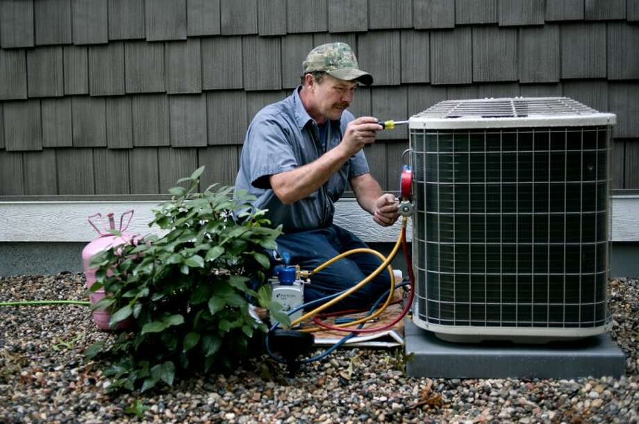 NICK KING | nking@mdn.netWild's Plumbing, Heating and Air Conditioning installer Thomas Wallace works on a new air conditioner outside a home constructed by Martelli Homes in Midland. Photo: Nick King/Midland  Daily News