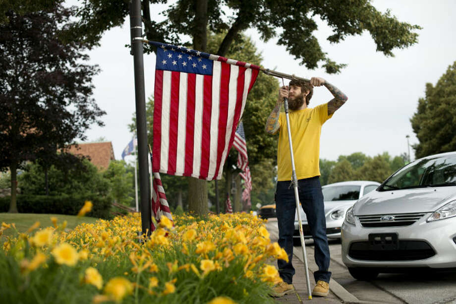 NEIL BLAKE | nblake@mdn.net Midland Parks and Recreation employee Daniel Dopp hangs flags near the Courthouse on Main Street on Wednesday morning. Dopp and other city workers were busy throughout the day preparing for the city's 4th of July festivities.