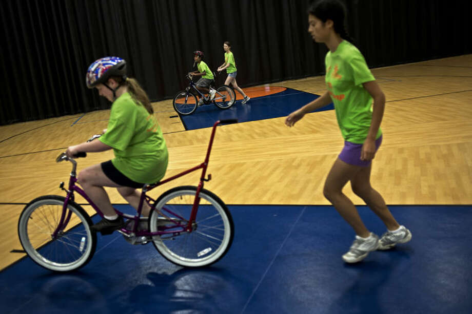 SEAN PROCTOR | sproctor@mdn.netAnshu Vungarala, 12, in the background, learns to ride his bike with the help of Samanta Manges, 16, while Jessica Lumbart, 16, does the same with the help of Jessica Sirias, also 16, during the iCan Bike camp at Midland Evangelical Free Church. Photo: Sean Proctor/Midland  Daily News