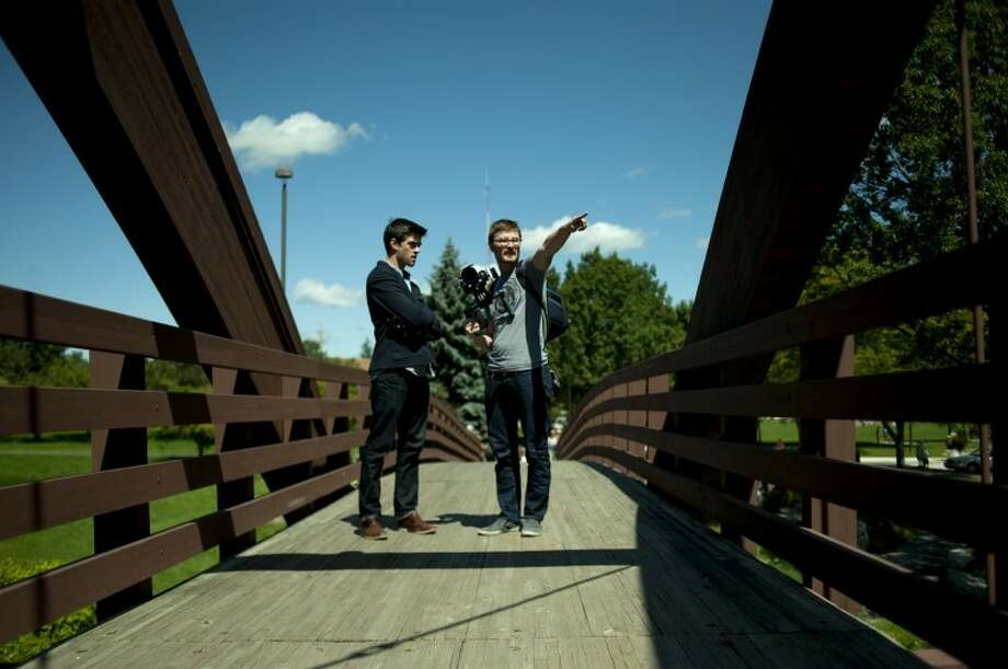 "Rob Bliss of Status Creative and cameraman Kevin Bubzynski discuss video angles before filming the Midland portion of a week-long film project about Michigan on Monday. Midland residents sang, ""Hands up if you're down with the mitten tonight,"" as they ran across the Tridge. Photo: Neil Blake/Midland  Daily News"