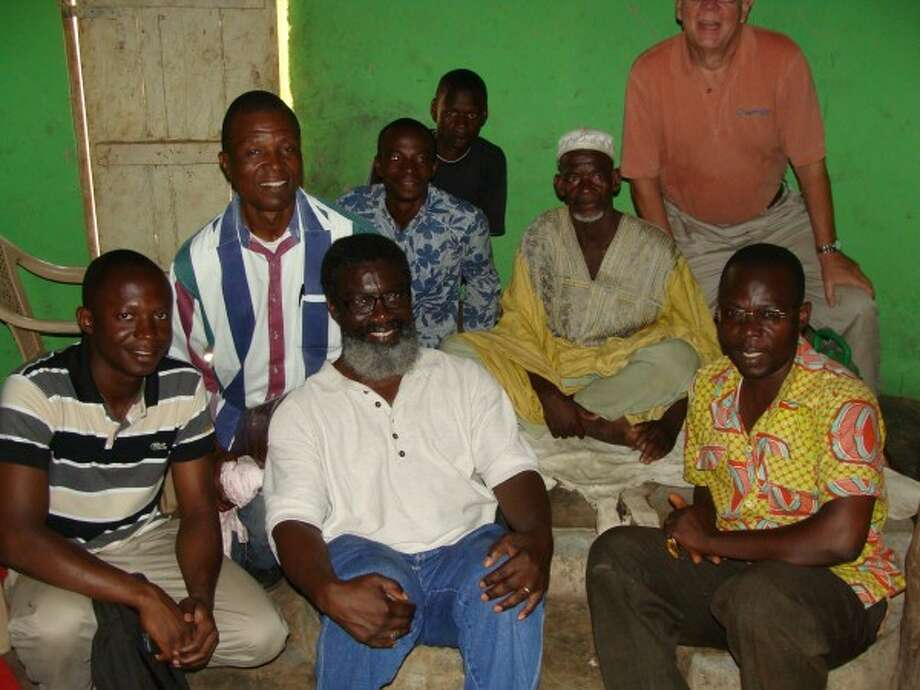 Photo providedVictor Atiemo-Obeng, front center, sits with the Rev. Josephus Hallie, Safe Water Team Michigan Executive Director Jim Bodenner, the Chief of Bagliga in Northern Ghana (in the hat) and a team of Safe Water Ghana filter installers.