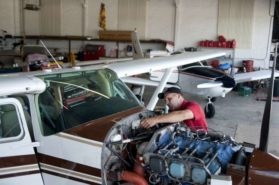 BRITTNEY LOHMILLER | blohmiller@mdn.netAircraft mechanic Todd Tarlton of Rosebush works on the engine of a Cessna 182 RG plane at the Mount Pleasant Municipal Airport. In October, Tarlton plans to open a second branch of Gateway Air Service at Jack Barstow Municipal Airport. Photo: Brittney Lohmiller