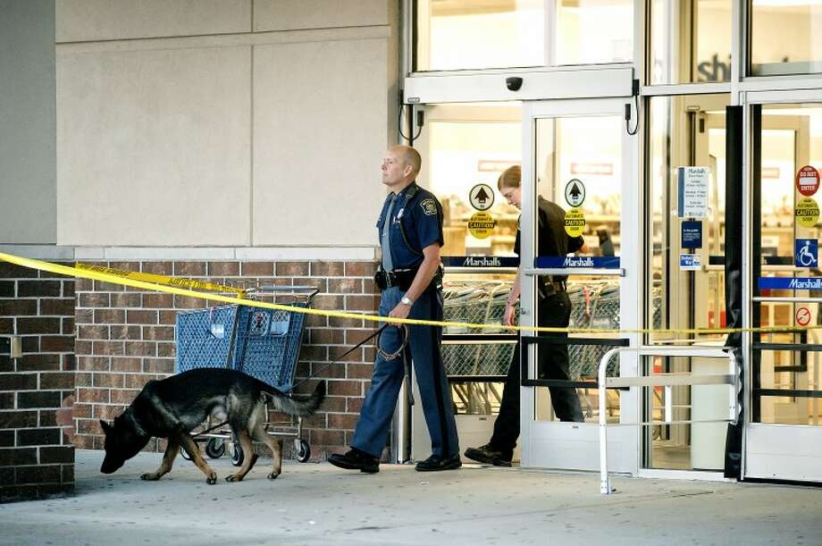 NICK KING | nking@mdn.net Bay City Post State Trooper Steven Escott, center, Midland police officer Jennifer Aldrich and Escott's explosion detection dog Beck exit the Midland Marshalls after investigating a bomb threat Friday evening. No explosives were found and the store is expected to be open Saturday morning. Photo: Nick King/Midland  Daily News