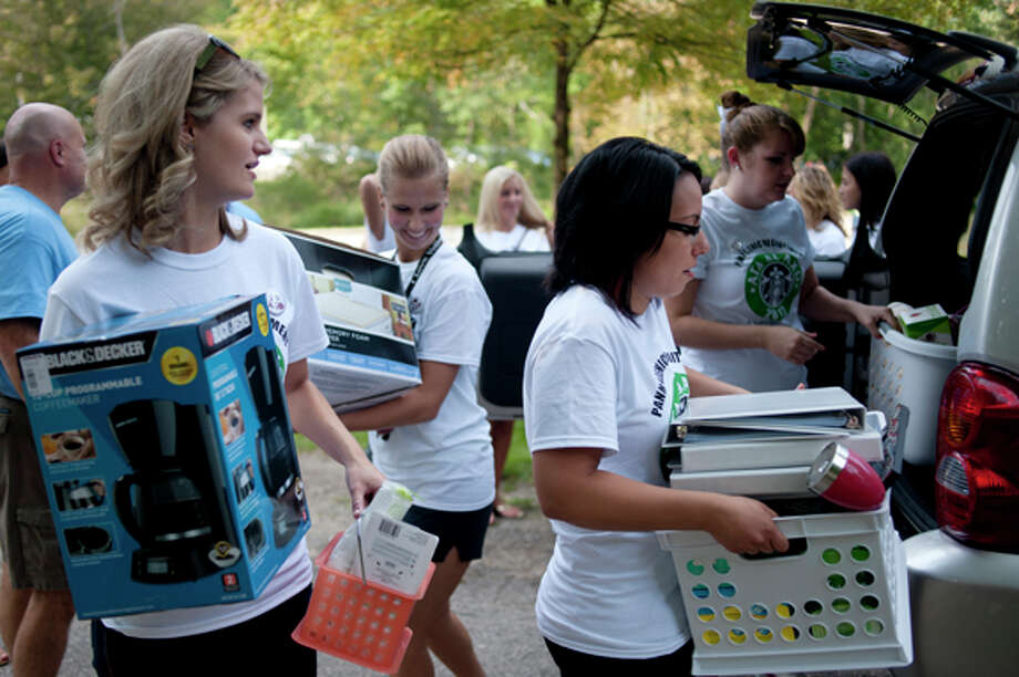 From left, Northwood University students and members of Alpha Gamma Delta sorority Devon Allen of Macomb, Laura Thomaswick of Toledo, Ohio, Racquel Fakhouri of Macomb, and Kate Baker of Saline help the new students carry their belongings to their dorm rooms at Miner Hall Friday morning. Photo: Brittney Lohmiller / Midland Daily News