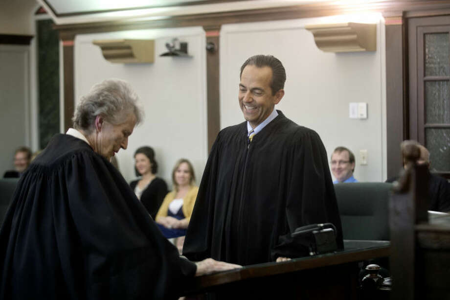 NICK KING | nking@mdn.netMidland County Circuit Court Judge Stephen P. Carras laughs before being sworn in by former Probate Judge Donna Morris Tuesday at the Midland County Courthouse. Carras was appointed to the position by the governor after former judge Jonathan Lauderbach resigned in March. Photo: Nick King/Midland  Daily News