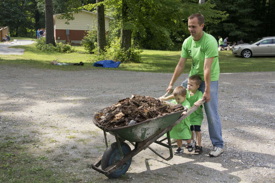 EMILY BROUWER | for the Daily NewsAdrian resident Brent Kubalek pushes a wheelbarrow full of leaves and wood with the help of his sons, Evander Kubale, 1, and Javis,4, on Saturday morning at Community of Christ Campground in Sanford.
