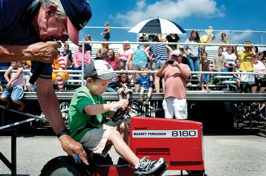 BRITTNEY LOHMILLER | blohmiller@mdn.netBob Wood, left, of Marlette, helps 4-year-old Kegan Garber of Midland start moving his tractor during the Pedal Pull Tuesday afternoon at the Midland County Fair. Many dozens of children signed up to try and pull miniature tractors and trucks loaded down with weights as far as they could. Photo: Brittney Lohmiller
