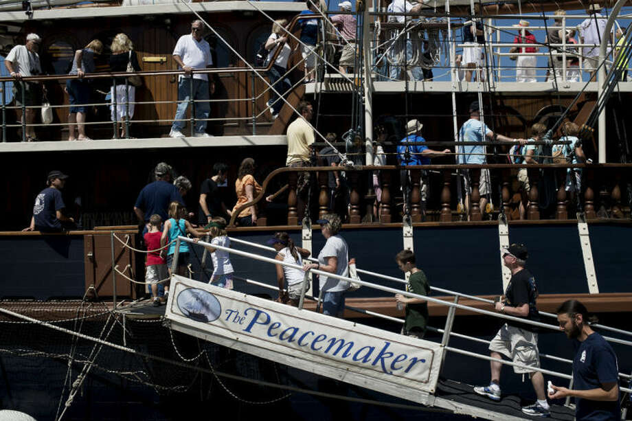 SEAN PROCTOR | sproctor@mdn.netPeople board the tall ship Peacemaker for a tour Friday during the Tall Ship Celebration in Bay City. Early in the day lines wrapped around the grassy knolls of Wenonah Park, with wait times nearing half an hour or more. Photo: Sean Proctor/Midland  Daily News