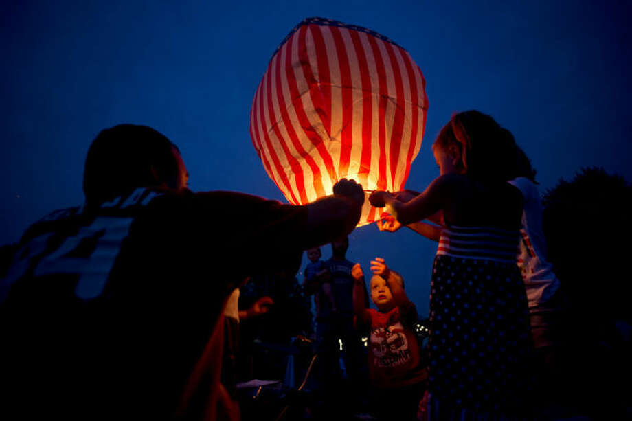 NEIL BLAKE | nblake@mdn.net Ray McLaughlin, left, of Midland, helps Layne Laubscher, 2, center, and Addisyn McLaughlin, 5, right, raise a lantern into the sky while waiting for the fireworks to start in Chippewassee Park on the Fourth of July. Photo: Neil Blake/Midland  Daily News