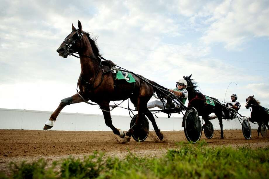 NEIL BLAKE | nblake@mdn.netJohn Putnam drives JPD ahead of James Ducett driving Stand Up during the 2-year old colt trot harness race at the Midland County Fair on Tuesday. Photo: Neil Blake/Midland  Daily News