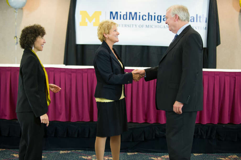 Photo providedDr. Ora Hirsch Pescovitz, left, executive vice president for medical affairs at the University of Michigan and CEO of UMHS, observes as MidMichigan Health President and CEO Diane Postler-Slattery congratulates Doug Strong, CEO of the U-M Hospitals and Health Centers, on the completion of an affiliation agreement.