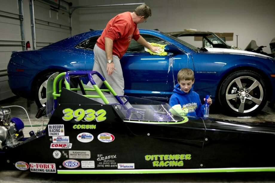 NICK KING | nking@mdn.netCorbin Dittenber, 10, cleans up his junior dragster as his father, Richard, cleans his Camaro in their garage. While racing is a great way for Corbin to compete and make friends, Richard says it's also a way for the father and son to bond over a common interest. Photo: Nick King/Midland  Daily News
