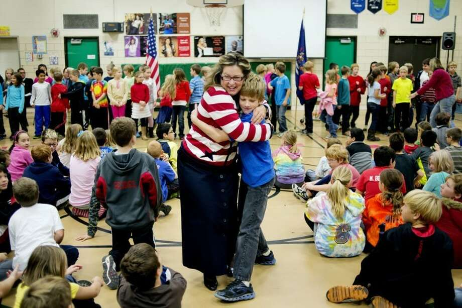 NICK KING | nking@mdn.netSeibert fourth grade social studies teacher Susan Shaffer, left, hugs student Trent Bergman during an assembly in the school gym honoring Shaffer for winning the Michigan History Foundation's Odyssey Award. Bergman, a fifth-grader, is a former student of Shaffer's. The award is given to two Michigan teachers who go above and beyond to find creative ways to teach Michigan history. Photo: Nick King/Midland  Daily News