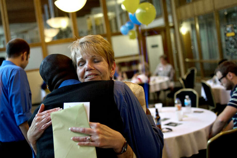NICK KING | nking@mdn.netSue Lombardo, right, hugs former Midland High School student Manny Sandow during her retirement party at the Midland Resort. Lombardo spent 19 years at Midland High School directing plays, coaching forensics and debate and as a teacher. Photo: Nick King/Midland  Daily News