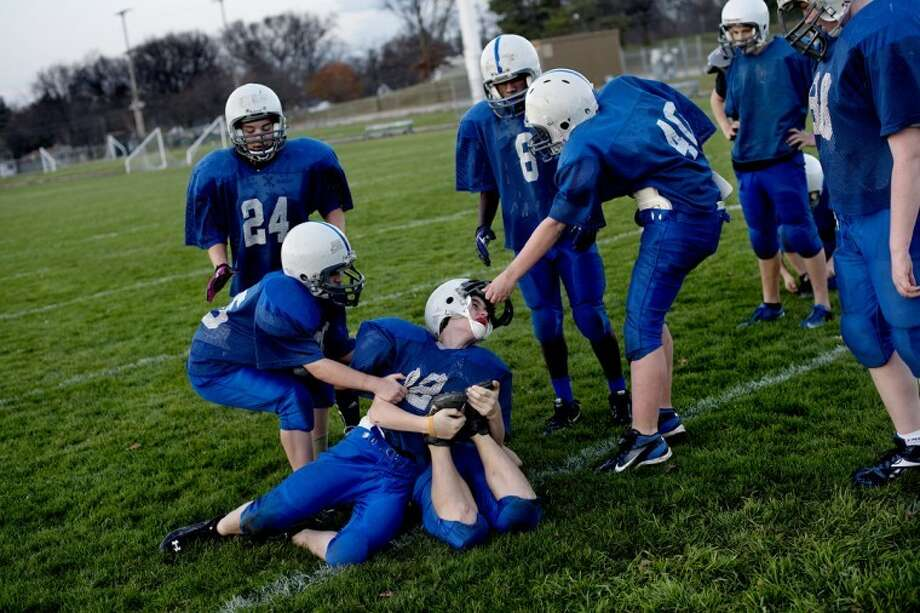 SEAN PROCTOR | sproctor@mdn.netDylan Draves, center, jokingly pins down teammate Hunter Clipper while Nick Kerkau, left, and Gary Yurgaites, right try and pull him off Sunday, Nov. 11, during the team's final get together a week after defeating Jefferson 28-12 in the final game of Central's football program. Photo: Sean Proctor