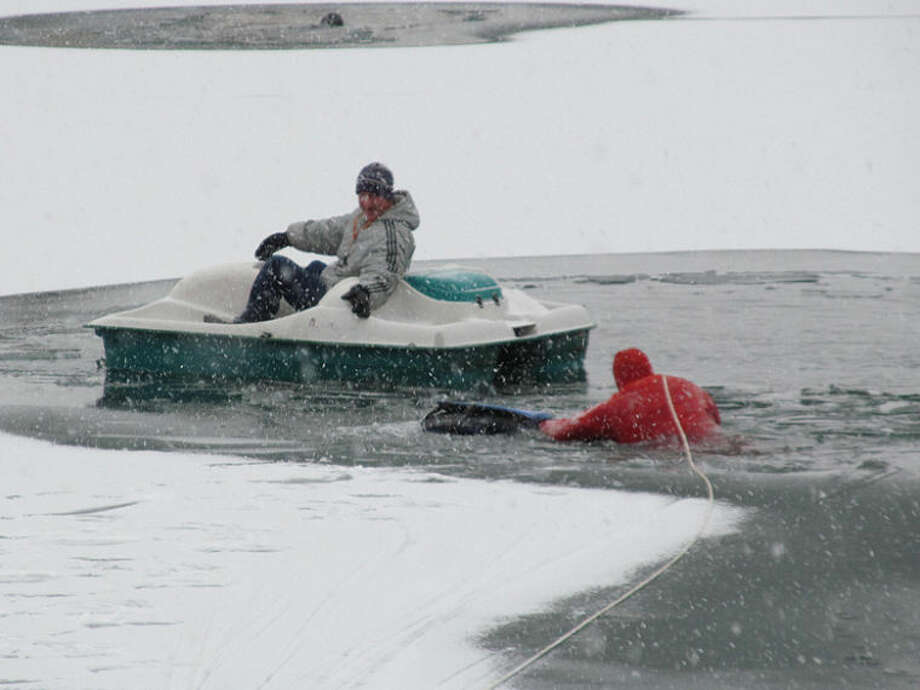 Photo courtesy of Midland County Sheriff's OfficeMidland County Sheriff's Deputy Tom Anderson swims to Gary Bellaver, delivering a personal flotation device and a rope. Bellaver had become stranded on the private lake after attempting to rescue his dog, Dakota, after she fell through the ice.