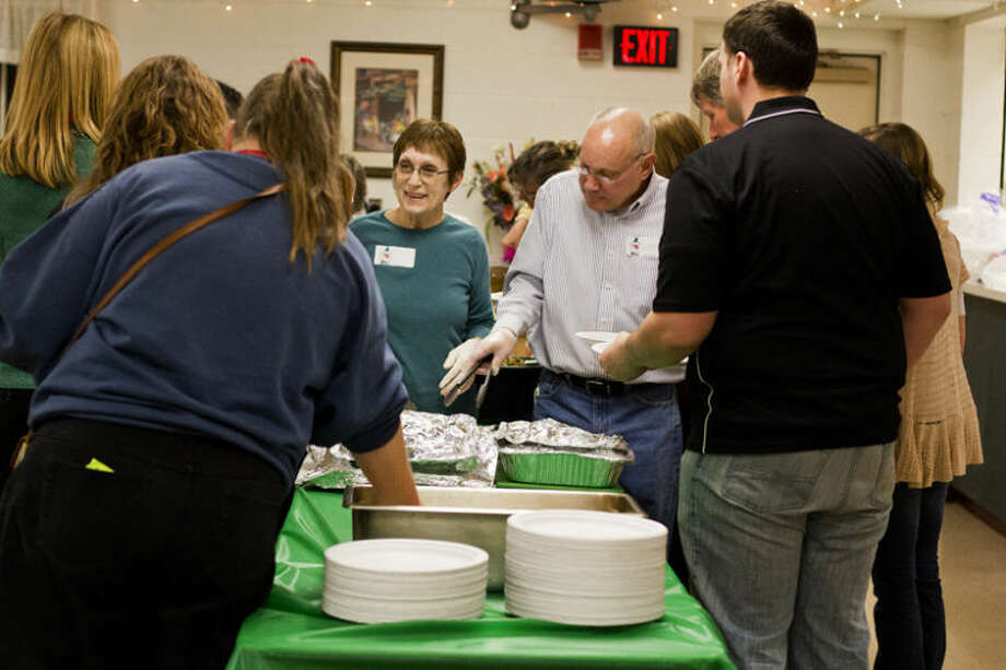 EMILY BROUWER | For the Daily News Sanford residents Dawn Plumer, 65, and Bryon Plumer, 66, serve food to guests at a Christmas event at the West Midland Family Center on Friday evening. The event was a joint effort by Big Brothers Big Sisters, Friends of Whispering Pines and the West Midland Family Center.