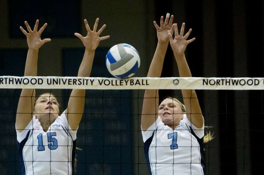 NICK KING | nking@mdn.netNorthwood's Ally Hoomaian, left, and Kristin Perschon block the ball in the third set of their match Wednesday during the quarterfinals of the GLIAC Volleyball Tournament at Northwood University. For more photos of the match, click on the yellow gallery link. Photo: Nick King/Midland  Daily News