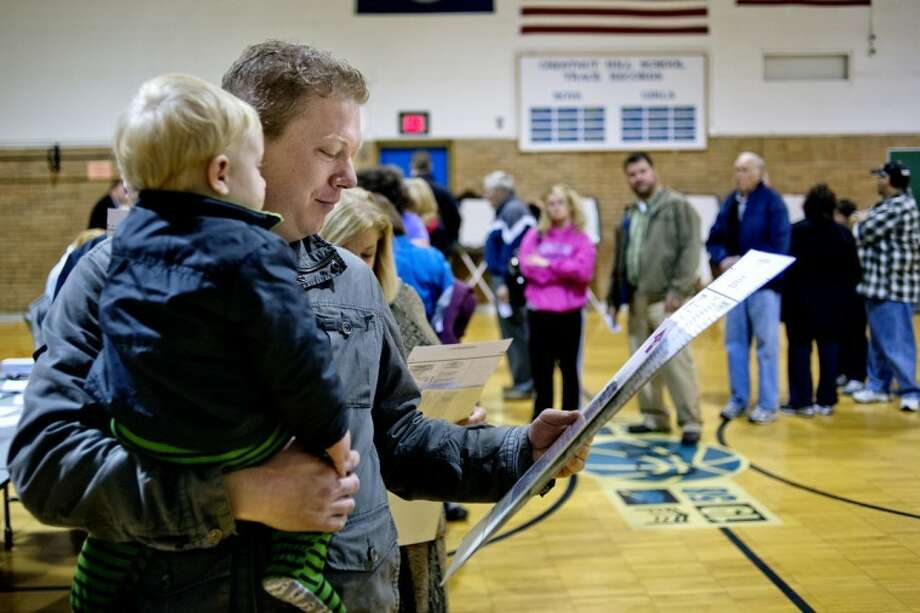 NICK KING | nking@mdn.netMike Bruce looks over his ballot with his 1-year-old son, Geofrey, as he waits to vote this morning at Chestnut Hill Elementary. Photo: Nick King/Midland  Daily News