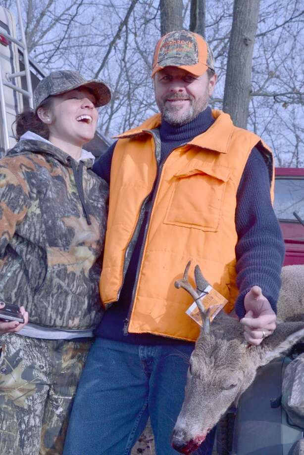 Steve Griffin | for the Daily NewsKen Martin and his daughter, Katie, both of Davison, share a laugh while they pose with a four-point buck they bagged on a landlocked private parcel within a large block of state-owned land between West River Road and M-18 north of Sanford on Thursday, the first day of the firearm deer season.