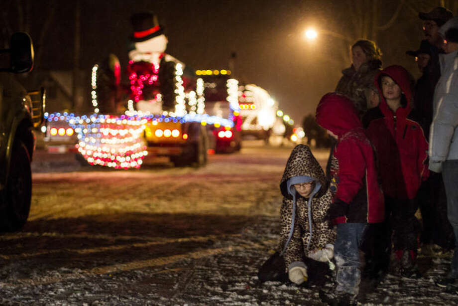 EMILY BROUWER | for the Daily NewsChildren pick up candy during the annual Coleman Christmas Parade on Saturday night. The parade has been going on for the past 30 years with different themes every year. This year, the theme was Learning the Christmas Spirit.