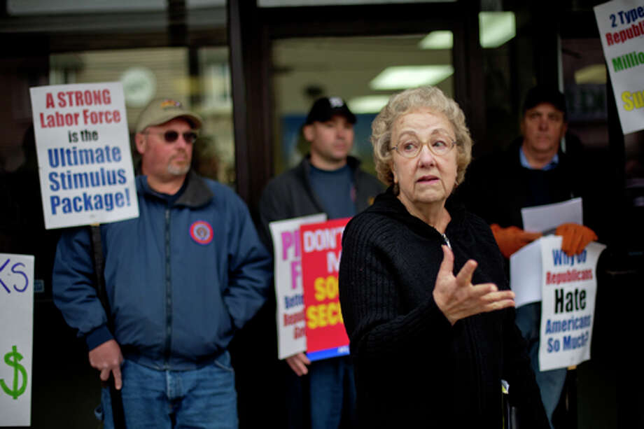 NICK KING | nking@mdn.net Margie Mitchell, executive director of the Michigan Universal Health Care Access Network, speaks during a demonstration against the Ryan budget plan Thursday outside Congressman Dave Camp's Midland office. Photo: Nick King/Midland  Daily News / Midland Daily News