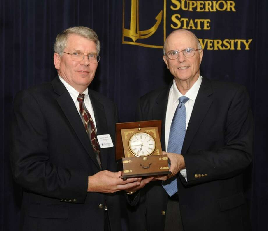 LSSU photo by John ShibleyDan Laur, left, accepts the LSSU Alumni Association's Outstanding Alumnus Award from his former political science professor, Richard Frey, during a special banquet on campus. The citation recognizes Laur as a person who is successful and who supports his alma mater with his time, talent and finances.