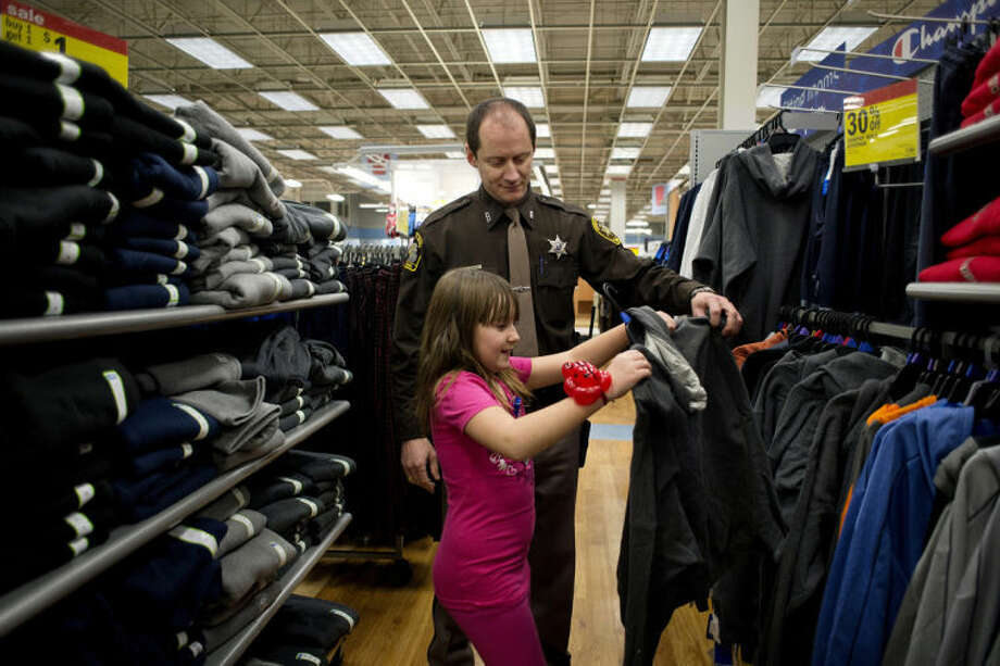 NICK KING | nking@mdn.netMidland County Deputy Myron Greene helps Holly Wetherell, 10, pick out a hooded sweatshirt for her dad as part of the Shop with a Hero event on Tuesday at the Midland Meijer. Wetherell picked out items for her entire family. Photo: Nick King/Midland  Daily News