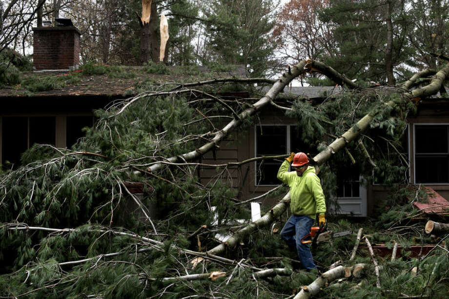 Mike Borch from Jack's Tree Service works on clearing a tree from the home of Anne Herron on Sylvan Lane after a storm in November. Photo: Neil Blake/Midland  Daily News