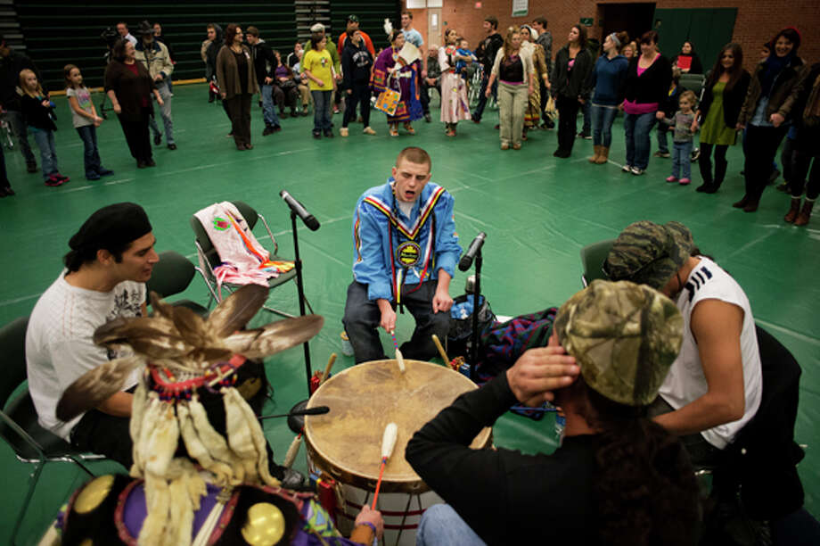 Charles Mackey Jr. of Mount Pleasant, center, keeps the beat with other drummers during the round dance at Delta College on Thursday. Round dances originated as social gatherings between tribes and continue to bring people together today. Photo: Neil Blake/Midland  Daily News / Midland Daily News