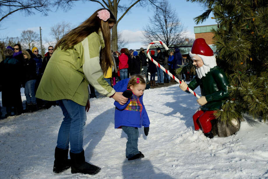NICK KING | nking@mdn.net Delaney Randall, left, guides her little sister Georgia Grenon, 1, past an elf as they wait in line to see Santa on Monday in Downtown Midland. The line outside the Santa House stretched down Main Street as many waited for their last chance to see Santa. Photo: Nick King/Midland  Daily News