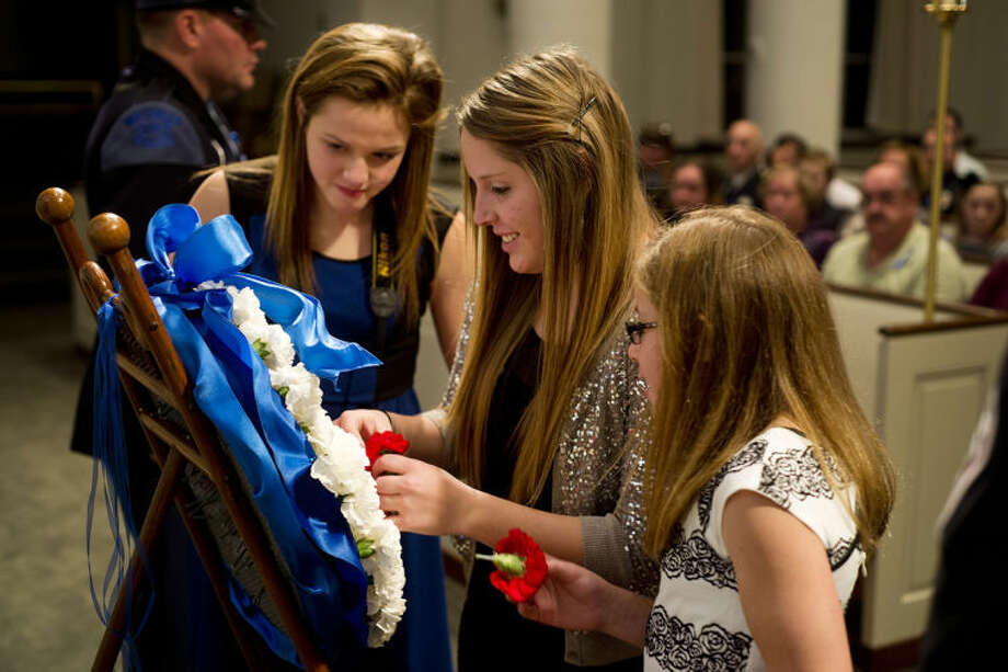 EMILY BROUWER | For the Daily NewsFrom left, Clare residents Gabby Sherwood, 14, Meagan Sherwood, 19, and Gwen Sherwood, 11, place flowers to honor those who have died in the line of duty at the Project Blue Light ceremony on Sunday evening.
