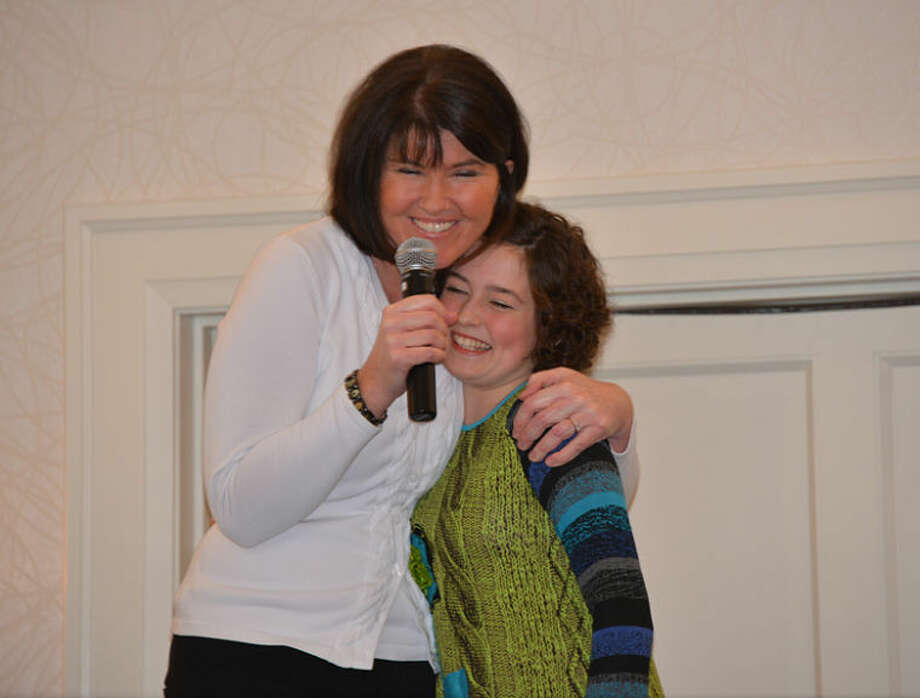 Photo providedEmcee Katie O'Mara hugs 12-year-old leukemia survivor and singer Mary Juengel.