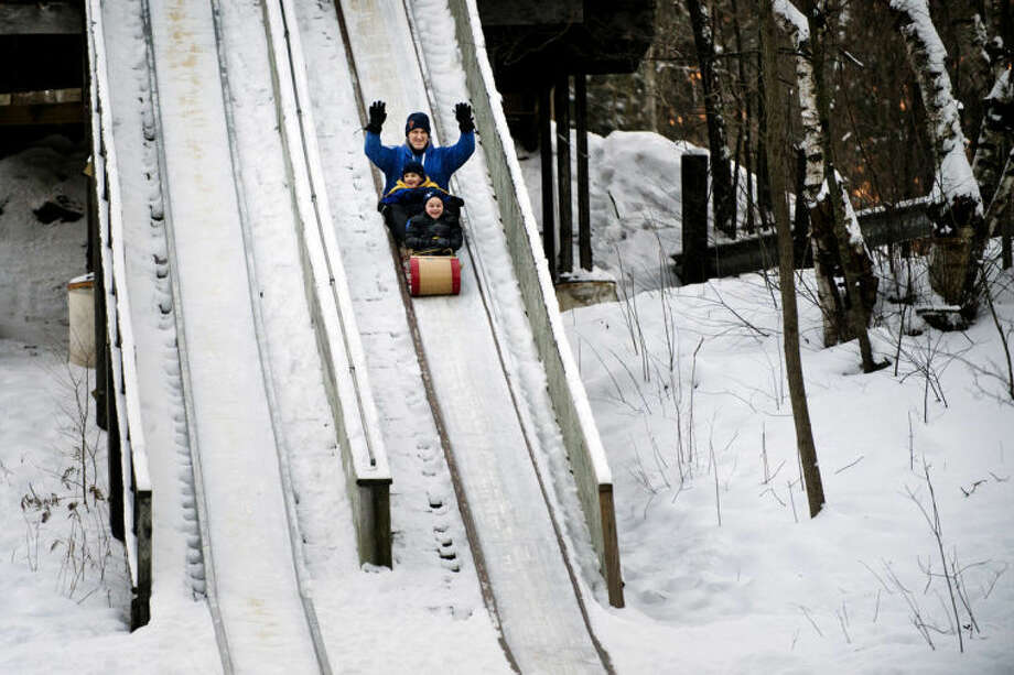 FILE — Chuck Carn rides on a toboggan with his sons, Sam, in front, and Logan, at Midland City Forest. Photo: Neil Blake/Midland  Daily News