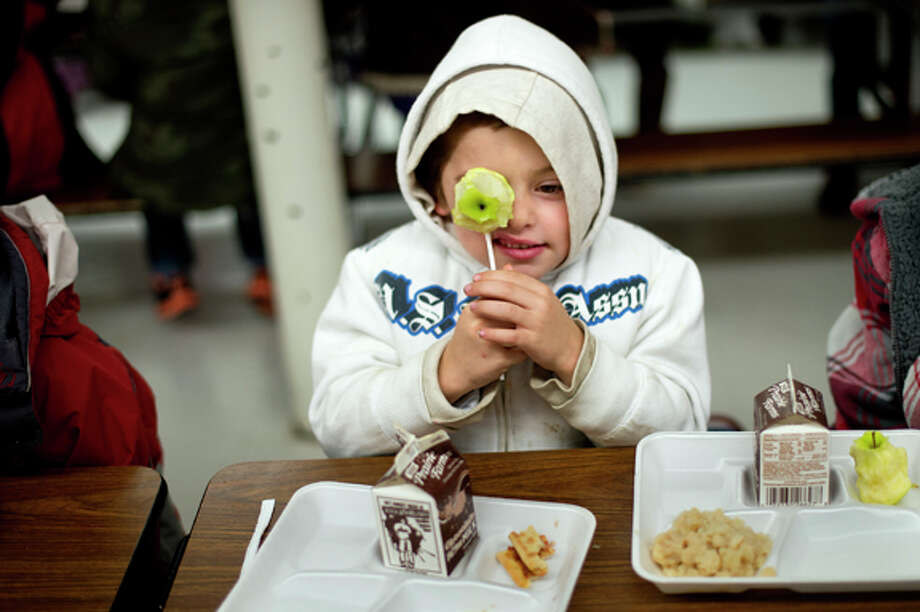 First-grader Mason Dachsteiner, 6, holds an apple up to his eye while eating lunch on Friday at Carpenter Elementary. Mason put the apple on a straw and joked with friends that he had an apple pop. Photo: Nick King/Midland  Daily News / Midland Daily News
