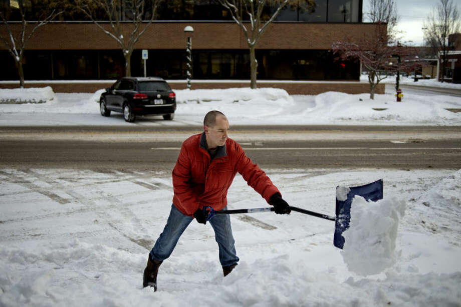NICK KING | nking@mdn.net Pharmacy manager Jason Baker shovels snow away from the front of The Apothecary Shoppe Pharmacies Monday before opening in on Main street in Downtown Midland. Baker said that since the business wasn't open on Sunday he had to clear away what the weekend storm left. Photo: Nick King/Midland  Daily News
